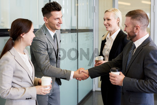Business People Shaking Hands in Hall