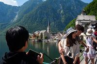 Hallstatt, Oesterreich, Asiatische Touristen fotografieren oberhalb des Hallstaetter See
