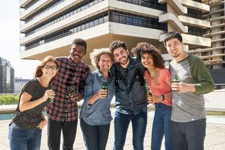 Junge Leute trinken Bier und feiern als Team