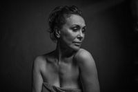 Portrait of a sensual fifty year old woman on grey studio background. Monochrome shot.