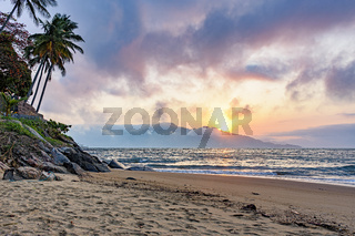 Sunset behind the mountains on a beach on Ilhabela Island