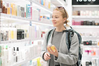Blond young female traveler wearing travel backpack choosing perfume in airport duty free store.
