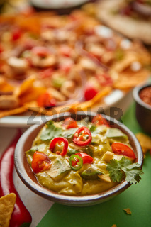 Close up on guacamole dip in bowl with various freshly made Mexican foods