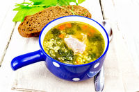 Soup with couscous and spinach in blue bowl on light board