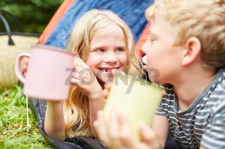Zwei Kinder als Freunde mit Tassen im Zelt