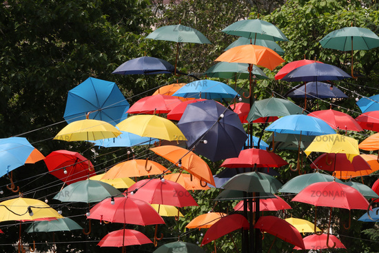 Multicolored umbrellas. Colorful umbrellas flying in the summer blue sky.