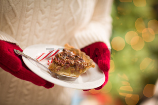 Woman Wearing Red Mittens Holding Plate of Pecan Pie with Peppermint Candy Against Decorated Tree and Lights