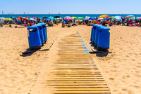 Valencia, Spain - June 23, 2019: Litter bins on a beach path for holidaymakers to keep the beach clean during the summer holiday season.