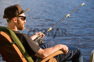 Mature man fishing from pier
