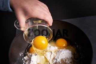 Kind giesst Ei in Ruehrschuessel