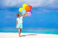Adorable little girl playing with balloons at the beach