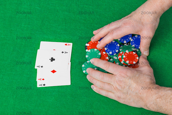 Hands with playing cards in casino