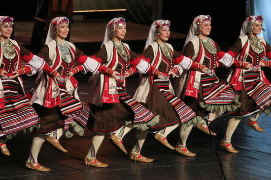 People in traditional folklore costumes perform folk dance Bulgarian horo on National folklore fair