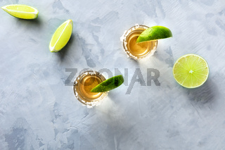 Golden tequila shots with limes and salt rims, shot from above with copyspace