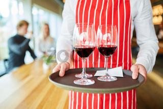 Servicekraft serviert Gläser mit Wein auf Tablett