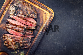 Barbecue dry aged wagyu flank steak sliced as top view on a burnt cutting board with copy space right