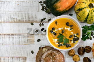 organic pumpkin soup in a white bowl framed by chestnuts pumpkins parsley and chestnut bread with copy space
