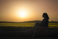 Silhouette of a girl and sunset over canola fields
