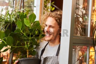 Junger Florist liefert eine Grünpflanze zum Kunden