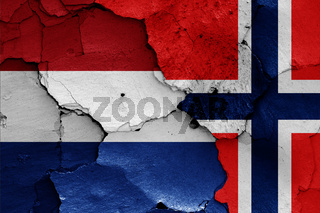flags of Netherlands and Norway painted on cracked wall