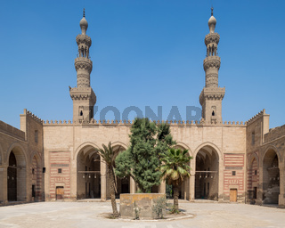 Courtyard of al Nasir Faraj ibn Barquq public historical mosque with two minarets, Cairo, Egypt