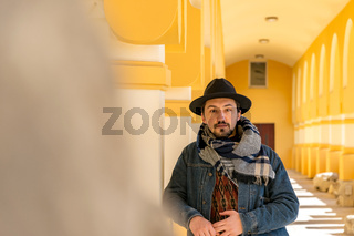 Portrait of a stylish handsome young man with a scarf outdoors.  A serious man wearing a scarf, hat and a denim jacket looking confident at the camera
