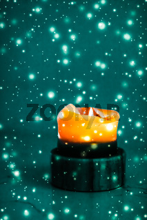 Orange holiday candle on green sparkling snowing background, luxury branding design for Halloween, New Years Eve and Christmas
