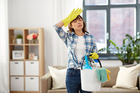 tired woman with bucket and cleaning stuff at home