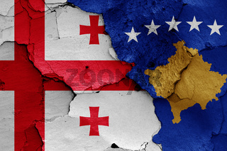 flags of Georgia and Kosovo painted on cracked wall