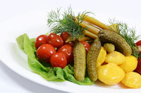 Different types of vegetables on white plate. Pickled cucumbers
