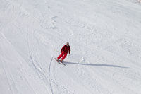 Skier on snowy sunlit ski slope at winter