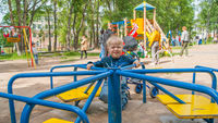 A three-year-old blond boy in a leisure park rides on a children's mechanical carousel. Mood Color - Blue
