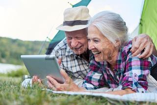 Paar Senioren mit Tablet Computer beim Zelten