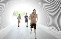 young men or male friends running in tunnel