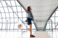 A woman walking in motion blur on white corridor with large windows.