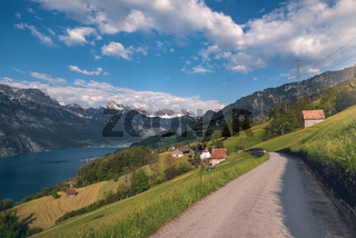 Road to Swiss village near a lake and the Alps