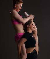 Redhead girl helping her friend do stretching