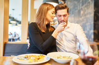 Junge Frau füttert ihren Freund beim Rendezvous