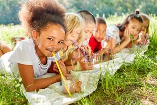 Kinder trinken Wasser mit Strohhalm im Sommer