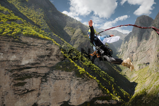 A man in a helmet jumps ropeup with an empty flag in the mountains. Extreme sports. Leisure