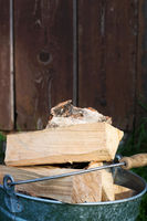 Bucketful of the firewood near a wood shed
