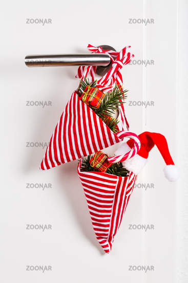 Small Christmas bag with branch and candy cane hanging on door handle on wite background