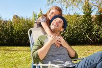 Tochter kuschelt mit ihrem Vater im Garten