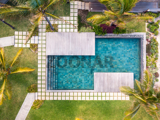 Aerial view of luxury hotel resort with swimming pool with stair and wooden deck surrounded by palm trees.