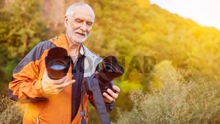 Fotograf beim Objektiv wechseln in der Natur