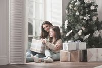 Mother and daughter unpack christmas gift