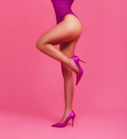 Woman legs on pastel pink backgrond