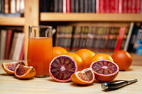 Glass of juice, knife and cut red oranges on a light wooden table.