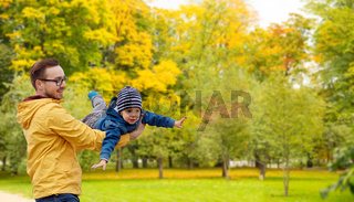 father with son playing and having fun in autumn