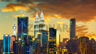 Kuala Lumpur City skyline with urban skyscrapers at sunset.